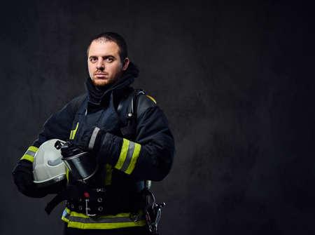 El retrato del estudio del bombero vestido con uniforme sostiene el casco de seguridad en su brazo. Foto de archivo - 88694356