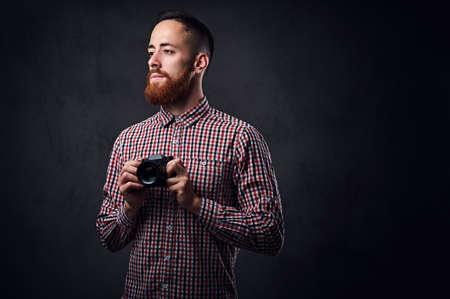 Redhead bearded male dressed in a red fleece shirt taking pictures with a compact camera.