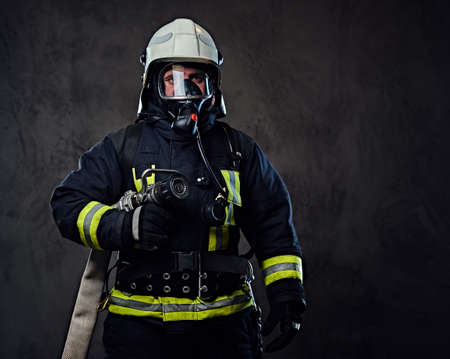 Studio portrait of firefighter dressed in uniform and an oxygen mask.