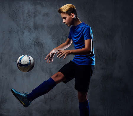 Blond teenager, soccer player dressed in a blue uniform plays with a ball. Stock Photo