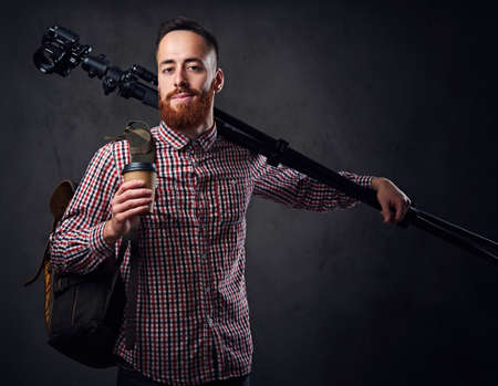 Redhead bearded freelance photographer with tripod and backpack.