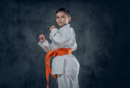 Preschooler boy dressed in a white karate kimono with orange belt.