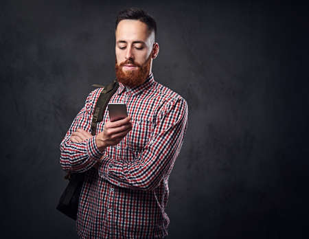 Redhead bearded hipster male in a red fleece shirt holds smartphone over grey background. Reklamní fotografie