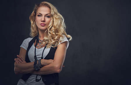 Studio portrait of blonde female dressed in white t shirt and waistcoat over grey background.