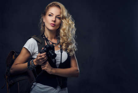 Studio portrait of blonde female backpacker holds a compact digital camera.