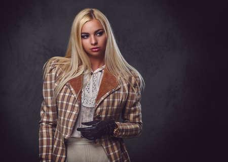 Studio portrait of old fashioned blonde female on grey background. Stock Photo