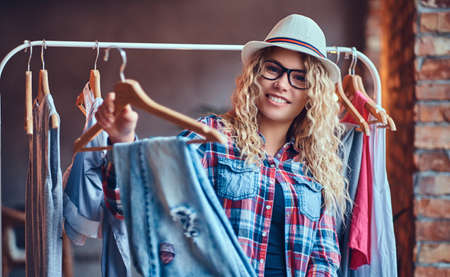 Positive blonde female in black eyeglasses chooses fashionable clothes on the coat rack.