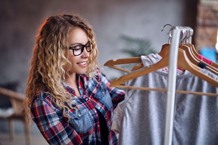 specific: Positive blonde female in black eyeglasses chooses fashionable clothes on the coat rack.
