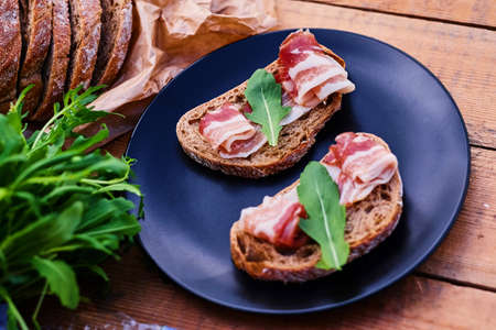 Bread with ham and herbs on a black plate on a wooden table. Stock Photo