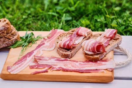 hams: Pan con carne gourmet en un escritorio de madera sobre fondo verde césped.