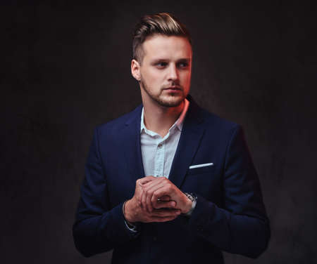 A man dressed in a suit over dark grey background. Stock Photo