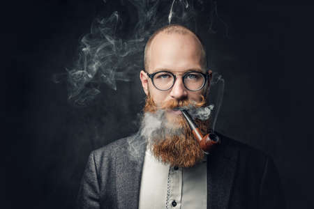 A man smoking pipe over grey background. Banco de Imagens