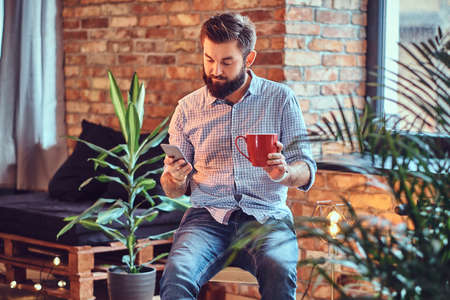A man drinks coffee in a room with loft interior. Stock Photo