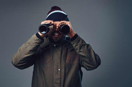 Muž, který hledá přes láhev piva.
