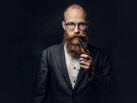 A man smoking pipe over grey background. 免版税图像