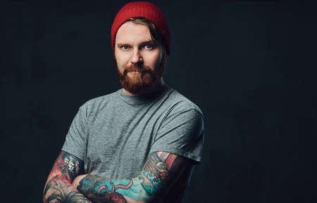 Tattooed bearded male over grey background. Reklamní fotografie