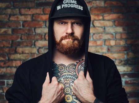 Tetovaný vousatý muž nad zdi cihly. Reklamní fotografie
