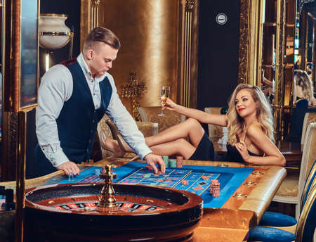 A man and woman play roulette.