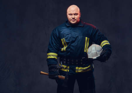 Firefighter holds the axe. 스톡 콘텐츠