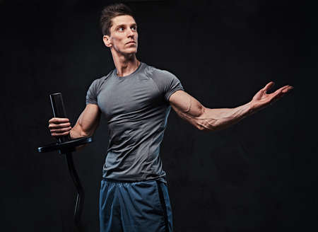 Athletic male holds barbell over grey background. Stock Photo