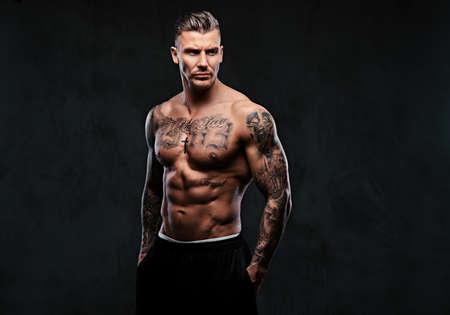 A muscular tattooed man on a dark background. Standard-Bild