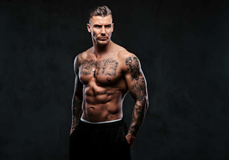 A muscular tattooed man on a dark background. Archivio Fotografico