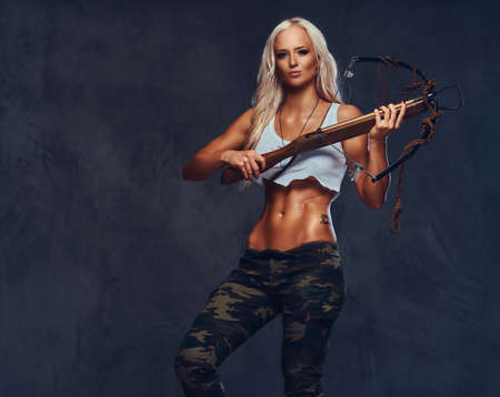 A woman holds crossbow.