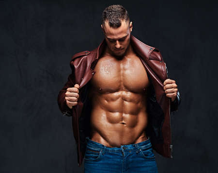Muscular male dressed in a jacket and jeans. Stock Photo