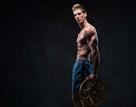 Ectomorph shirtless athletic male holds barbell weight. Stock Photo