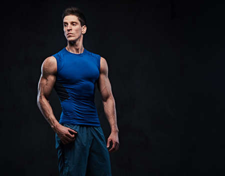 Shirtless muscular male over dark background.