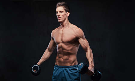 Shirtless athletic male doing shoulders exercises. Stock Photo