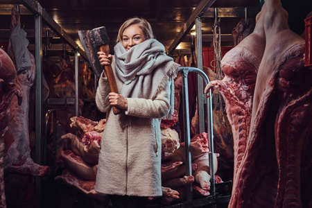 Blond female in a warm jacket in a meat freezer storage. Foto de archivo