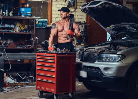Shirtless mechanic in a garage. Stok Fotoğraf