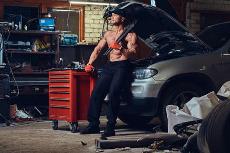 Shirtless mechanic in a garage. Stock Photo