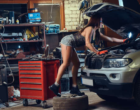 Female repairing a car.