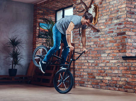 A handsome man with BMX in a studio.