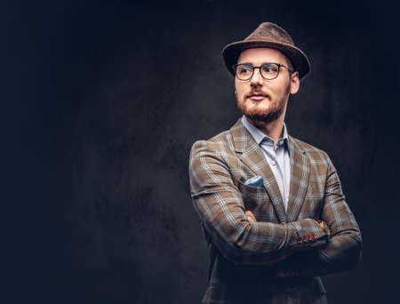 Studio portrait of a bearded hipster in hat and glasses wearing