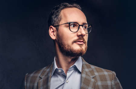 Studio portrait of a bearded hipster in glasses wearing a casual