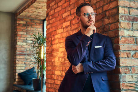 Portrait of a handsome bearded male wearing stylish suit standing