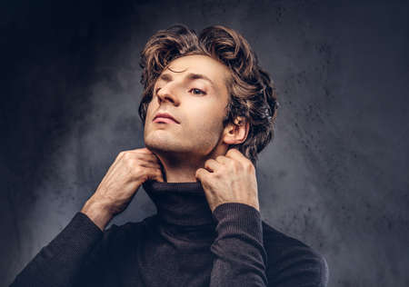 Portrait of a charismatic sensual male in black sweater. Imagens