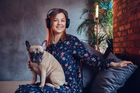 Happy blonde in casual clothes listening music and sits with a cute dog Stock Photo