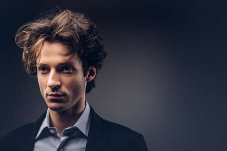 Studio portrait of a stylish sensual male with hairstyle in a casual suit