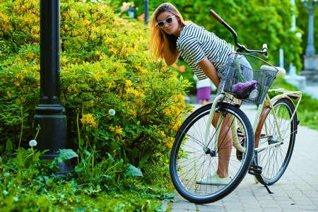 An attractive brunette female with a bicycle sniffing flowers in a park