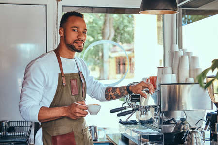 An African-American barista making a coffee with the professional coffee machine, at the coffee shop.