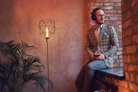 Portrait of a stylish man in a flannel suit and glasses listening music with the phone and headphones sitting on a window sill in a room with loft interior. Stock Photo