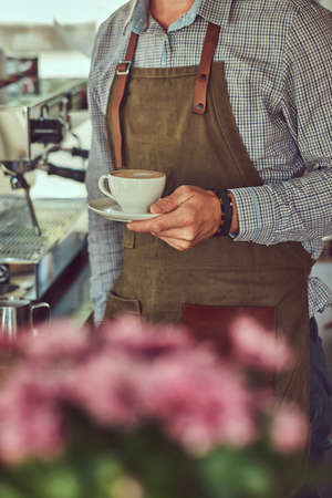 A professional barista making a coffee with the professional coffee machine, at the coffee shop. Stock Photo