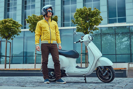 Handsome male wearing brown pants and yellow jacket, in sunglasses and helmet, standing near classic Italian scooter against a skyscraper. Stock Photo