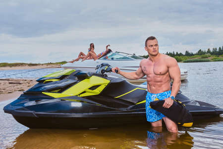 Handsome shirtless sportsman with a muscular body standing near jet ski on a seacoast. Banque d'images