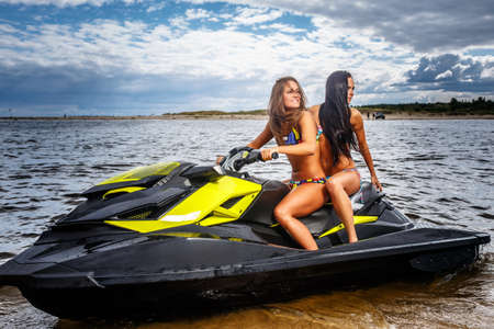 Two sexy girls in a swimwear, sitting on a jet ski, have fun at a leisure.