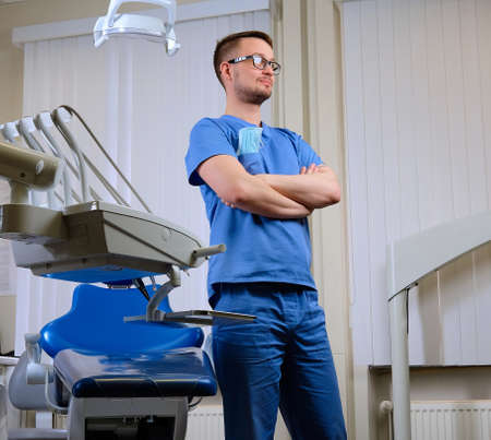 Handsome bearded male dentist in blue uniform and glasses, standing with crossed arms at a dentist clinic. Stock Photo